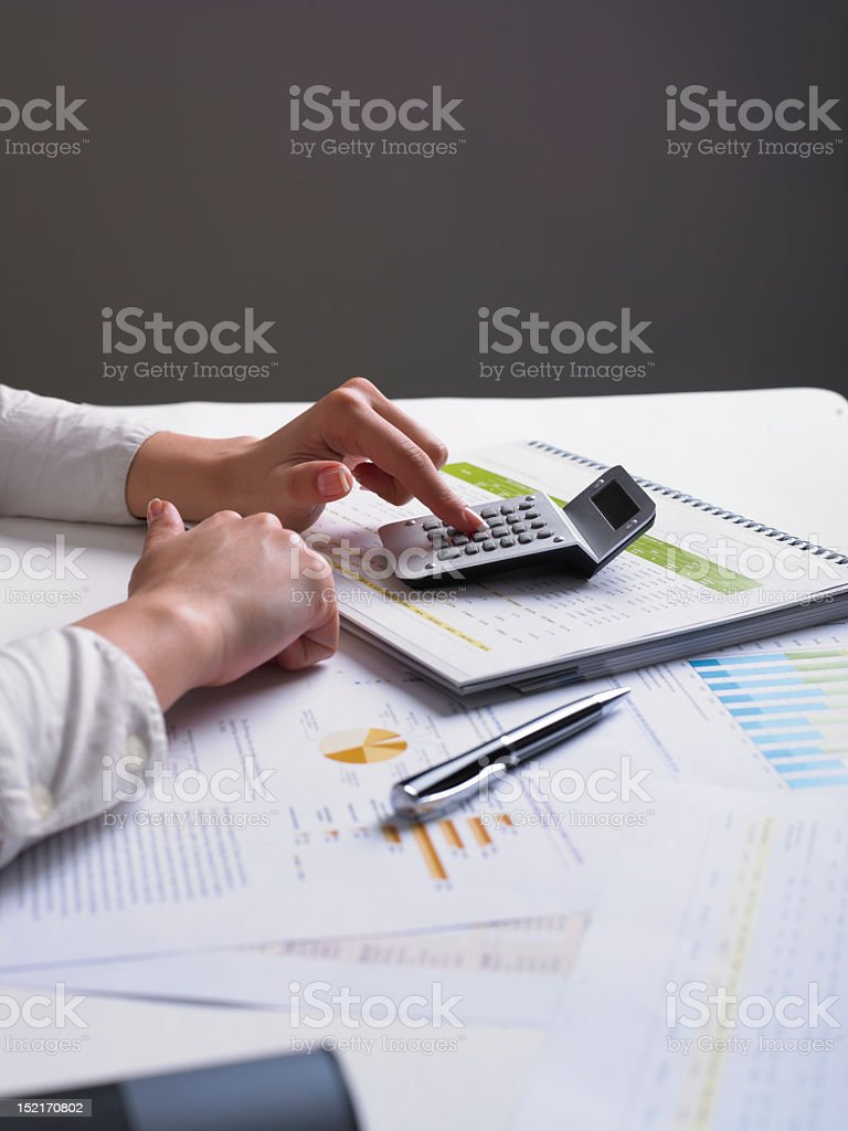 Human hands using a calculator to analyze business data royalty-free stock photo