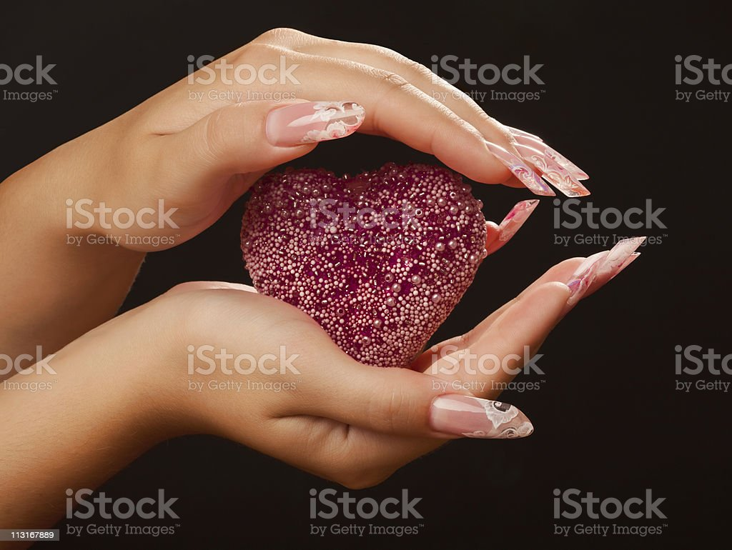 Human hands with beautiful manicure hold pink heart royalty-free stock photo