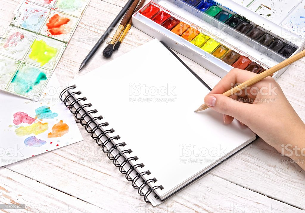 Human hands with pencil draws in notebook. stock photo