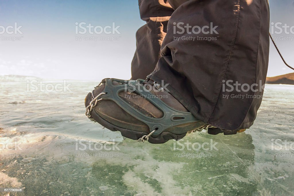 Human legs in hiking boot in ice crampons on texture stock photo