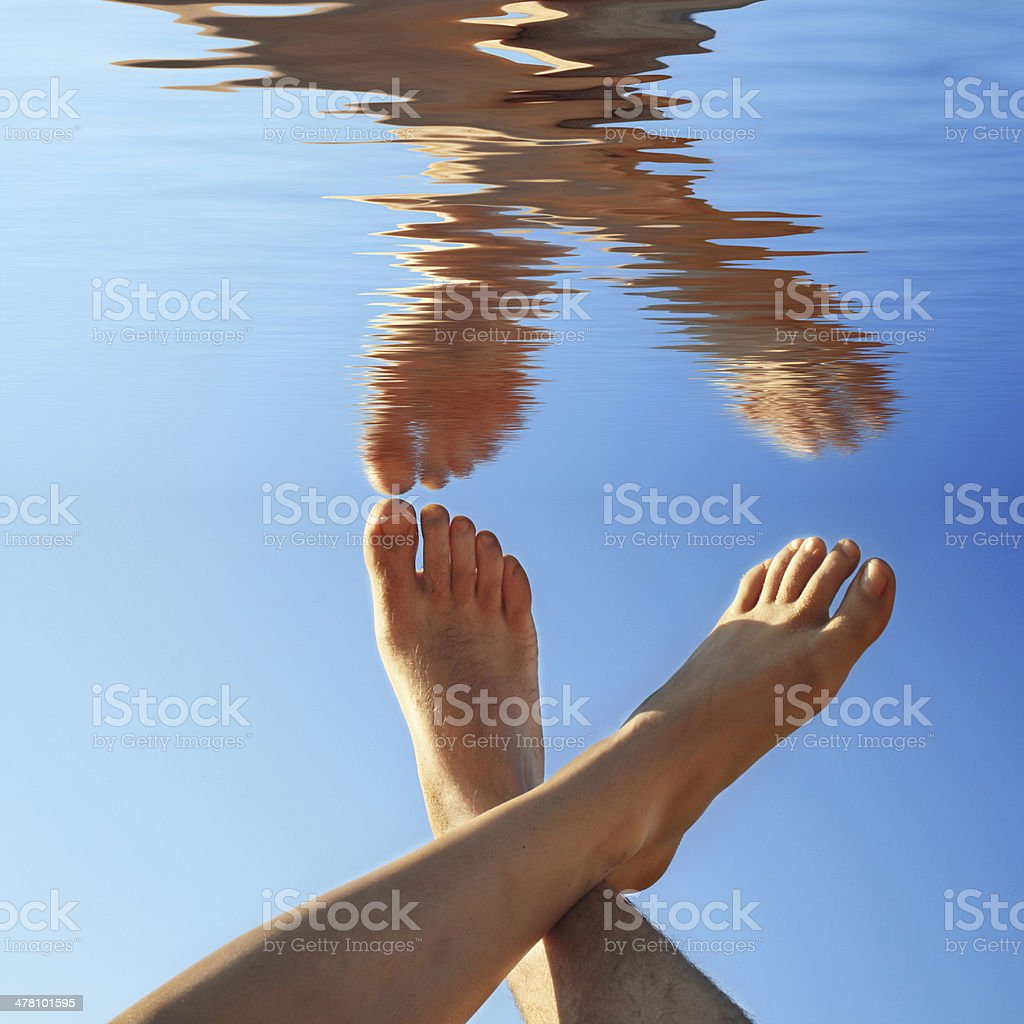 human legs on the blue water in summer royalty-free stock photo