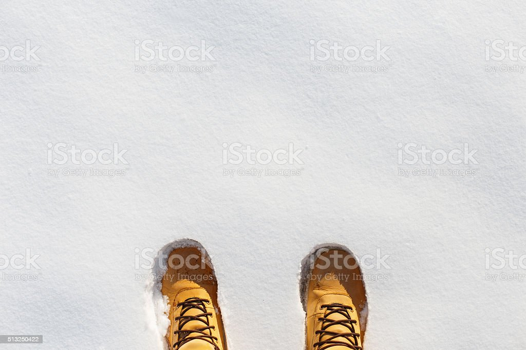 Human legs with leather yellow boots standing in the snow. stock photo