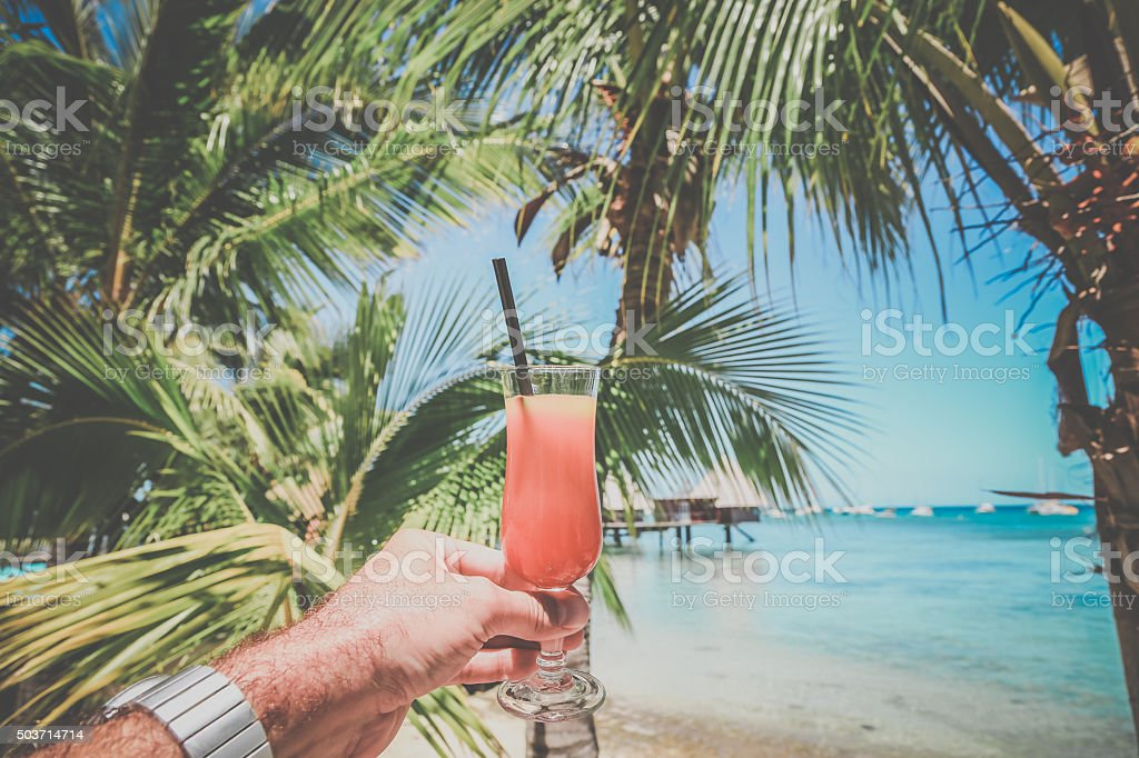 Human Man Hand Holding Cocktail at Tropical Beach Resort stock photo