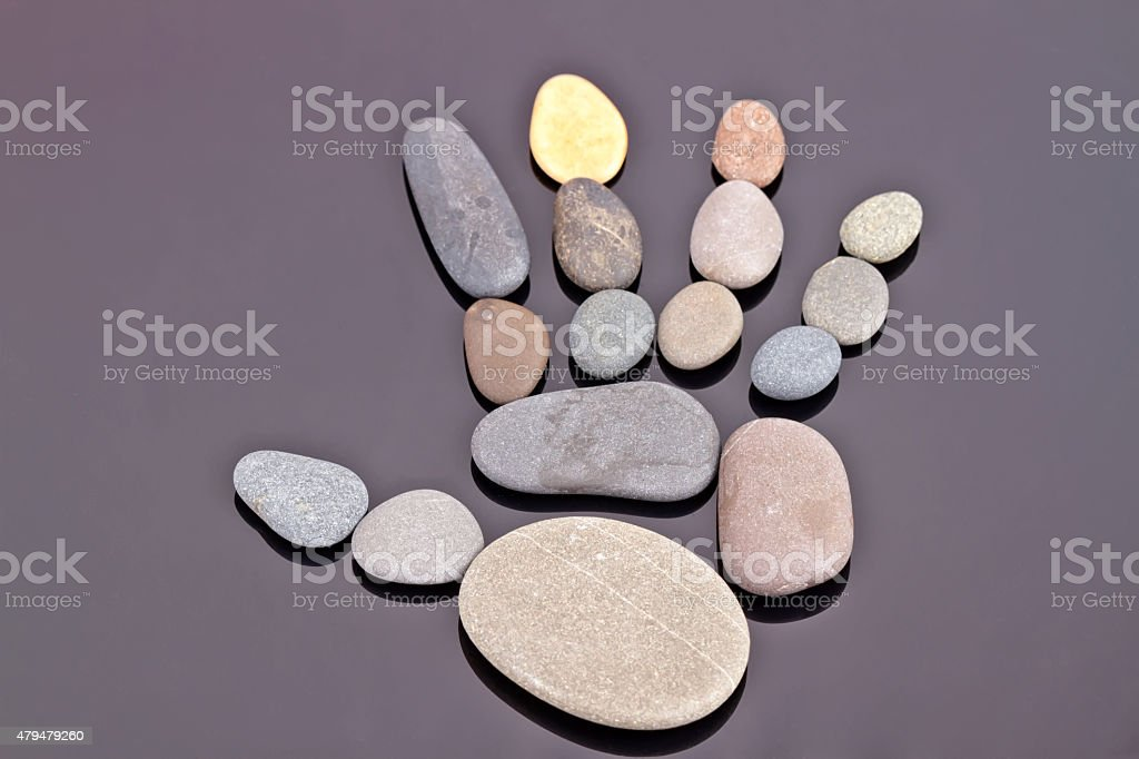 human palm is fine going out of small sea stones stock photo