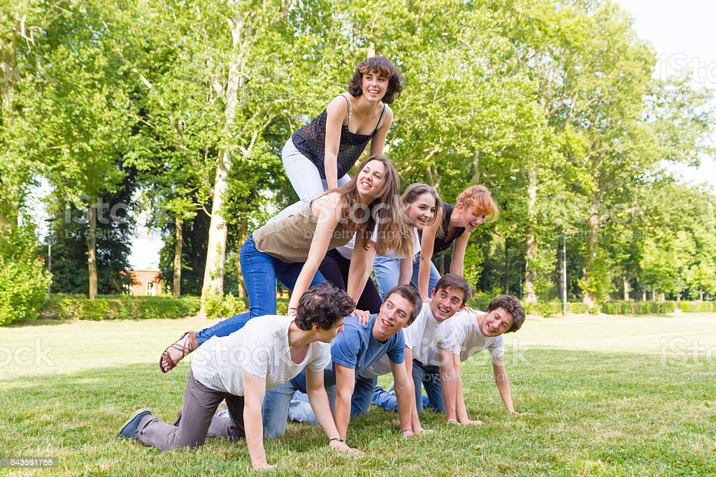 human pyramid teenagers in a park stock photo