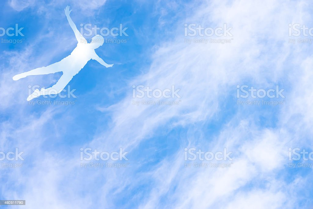 Human silhouette in flight against the sky stock photo