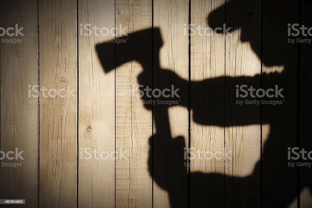 Human Silhouette with Axe in shadow on wooden background, XXXL stock photo