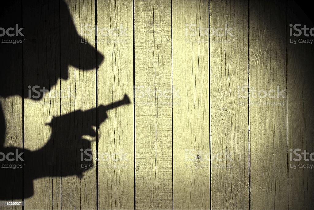 Human silhouette with handgun in shadow on wood background, XXXL stock photo