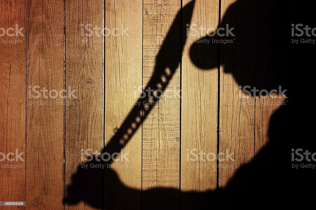 Human Silhouette with  Machete in shadow on wooden background, X stock photo