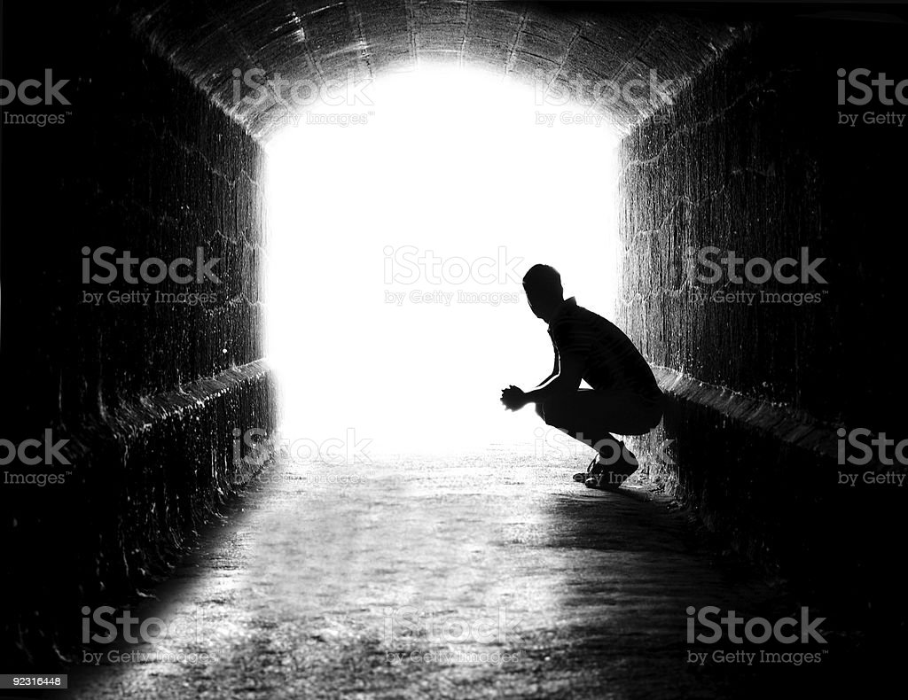 Human sitting silhouette (back-lit) in tunnel exit royalty-free stock photo