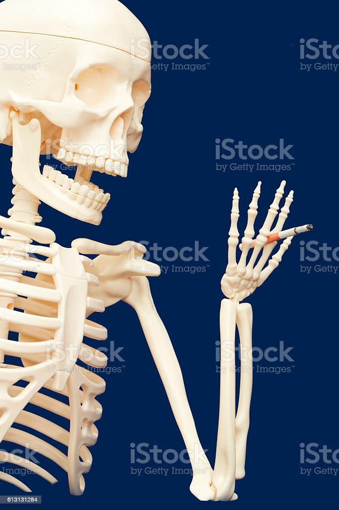 human skeleton smoking and using drugs - death stock photo