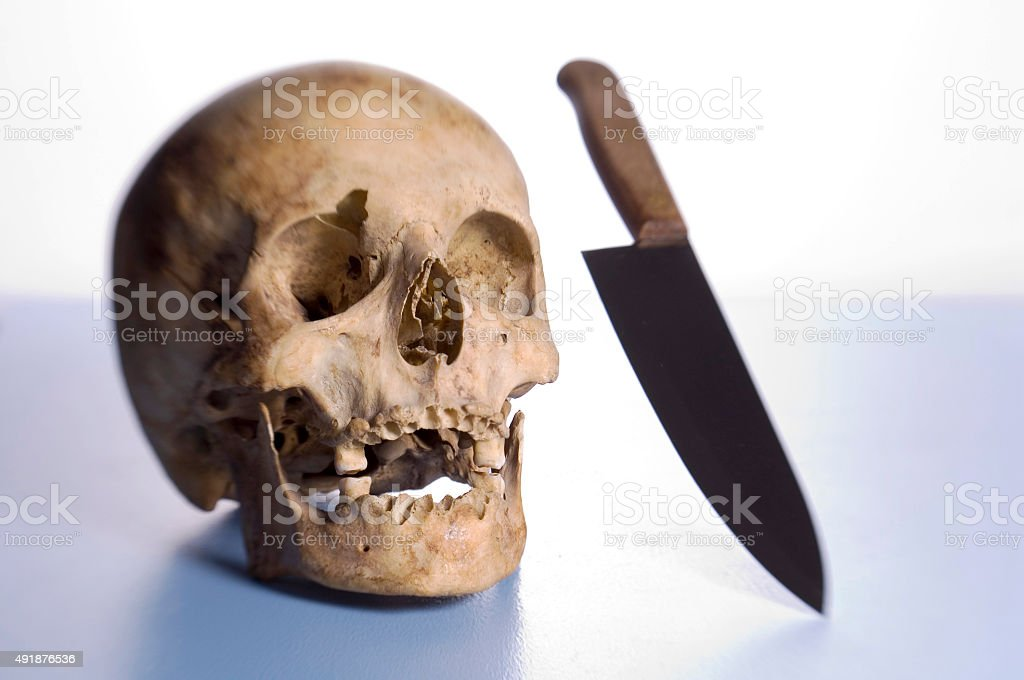 Human skull and knife stock photo