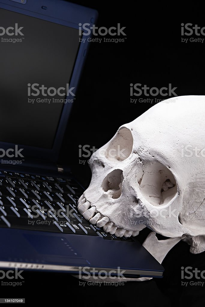Human skull eats up computer - virus metaphor royalty-free stock photo
