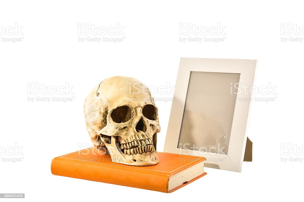 Human skull on orange book with picture frame o stock photo