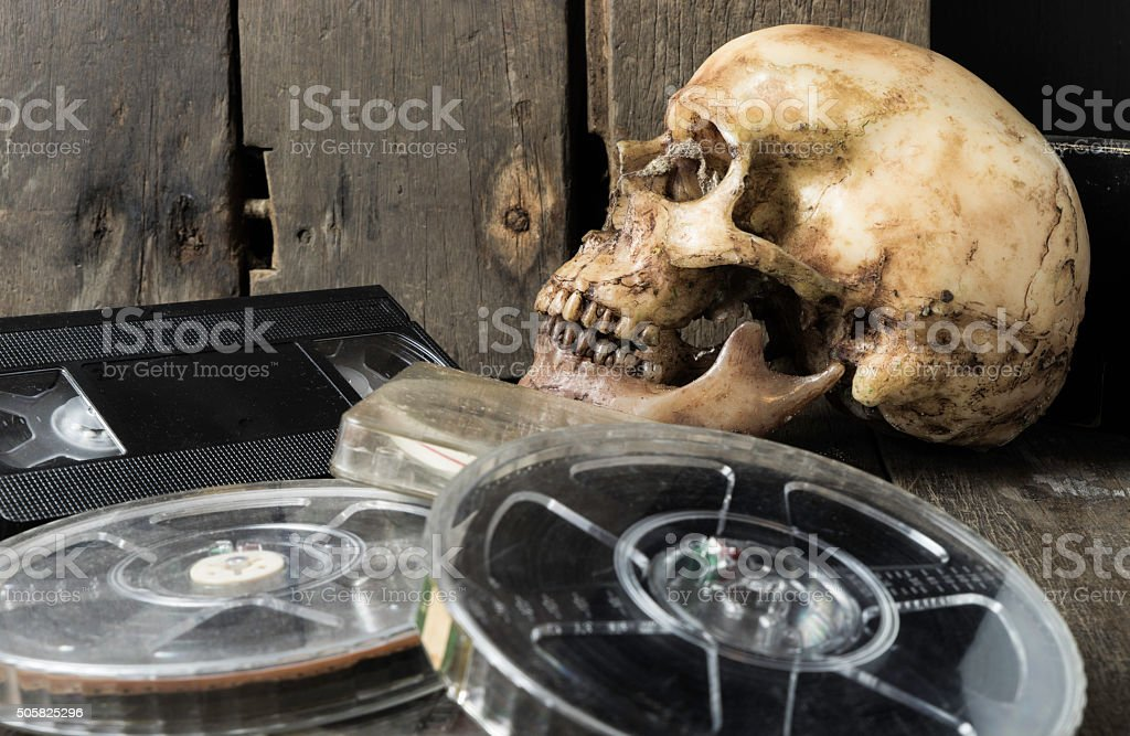 Human Skull Video tape and Film reel on wooden table stock photo
