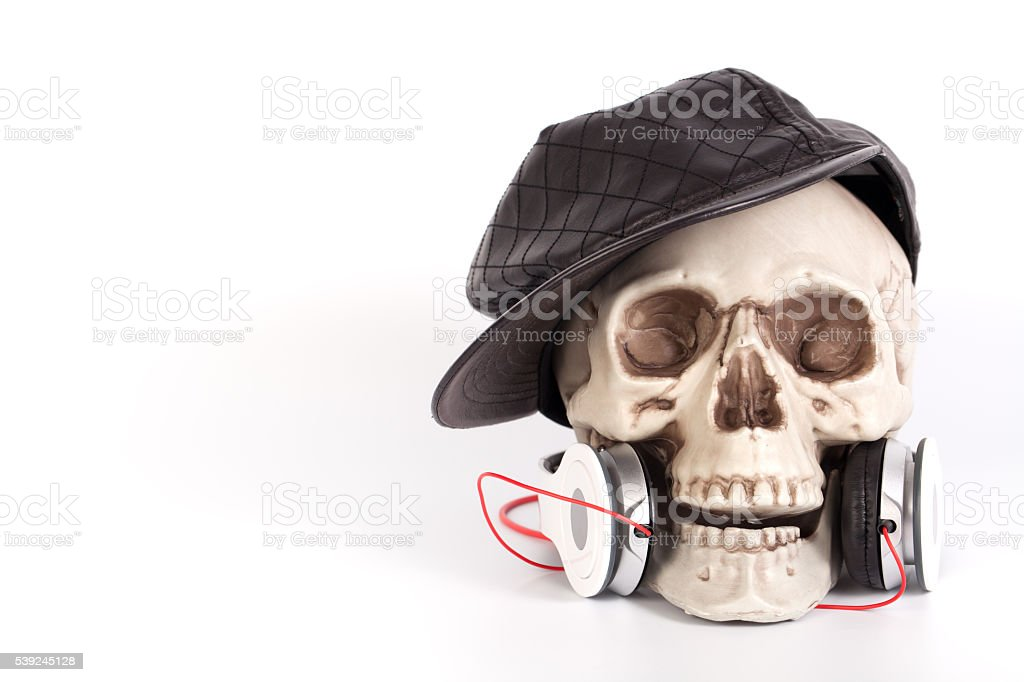 Human Skull wear black hat  listen to music by headset/headphone stock photo