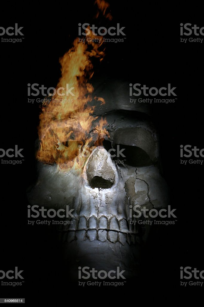 Human skull with burning eye socket stock photo
