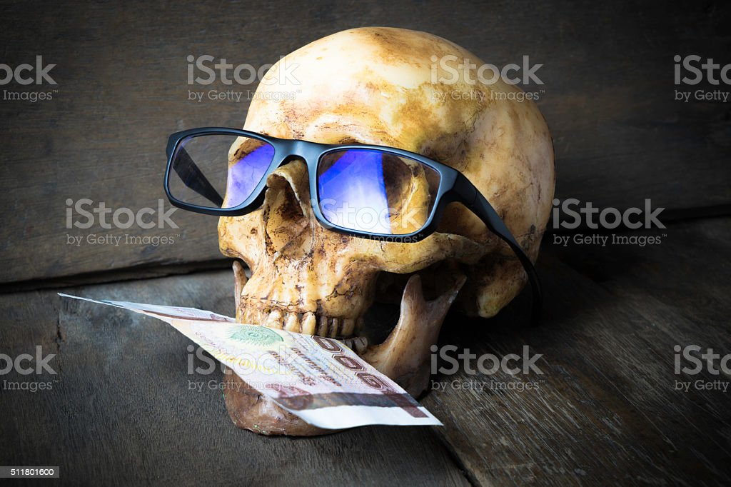 Human Skull with Glasses with Bank note in it's mouth stock photo
