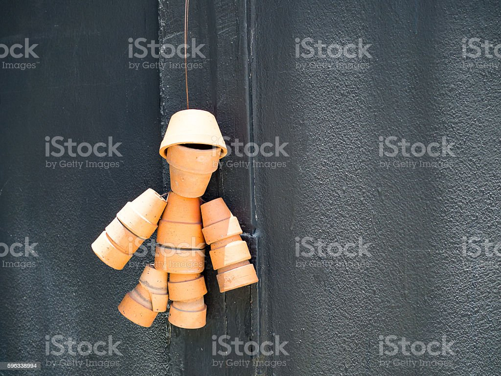 Human symbol made from small vase hang on black wall. stock photo