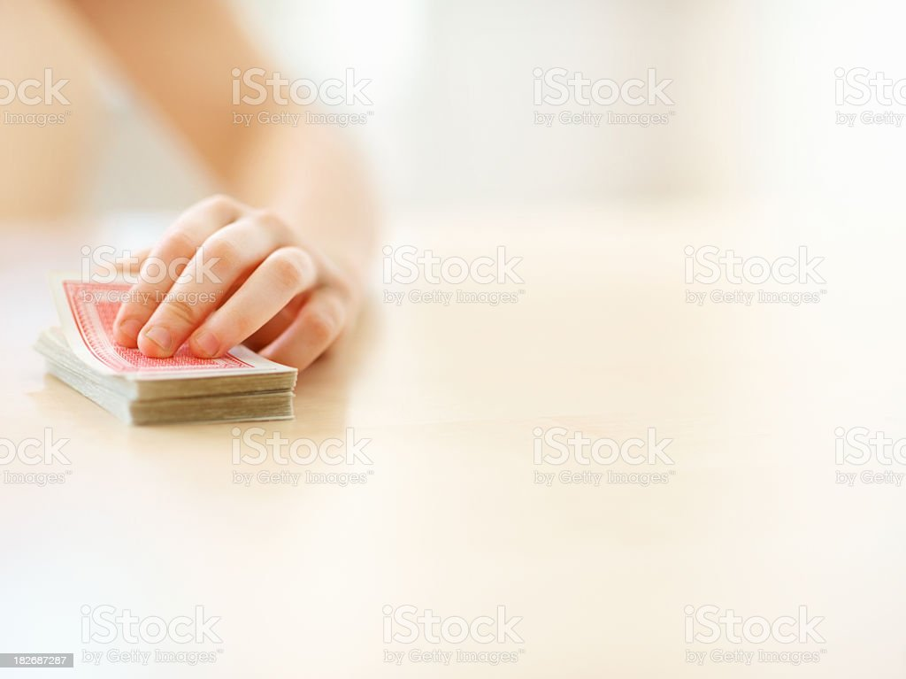 Human with a deck of cards on table stock photo