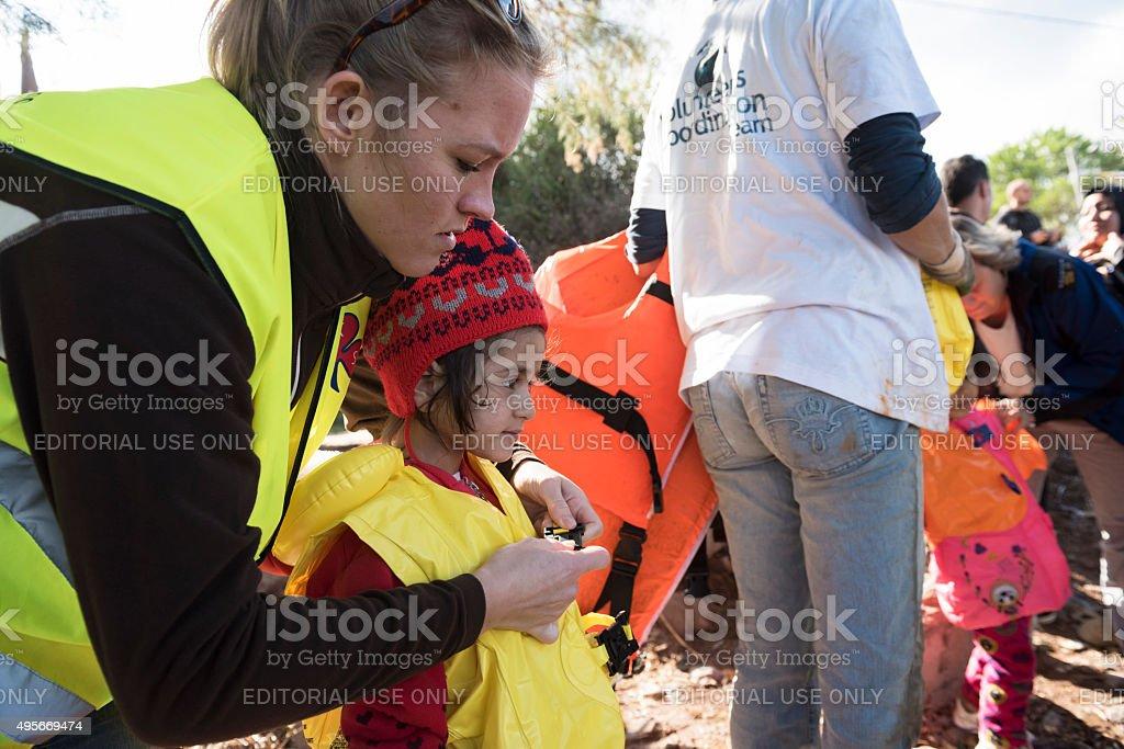 Humanitarian volunteer assisting migrants traveling to Europe stock photo