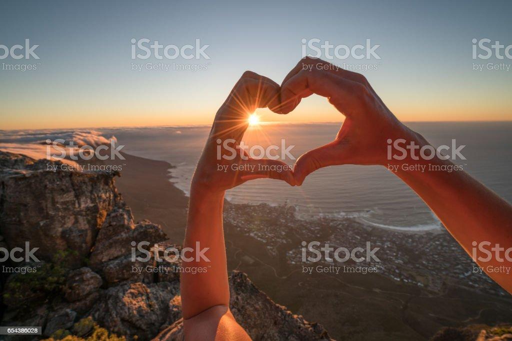 Human's hand making heart shape frame over coastline stock photo