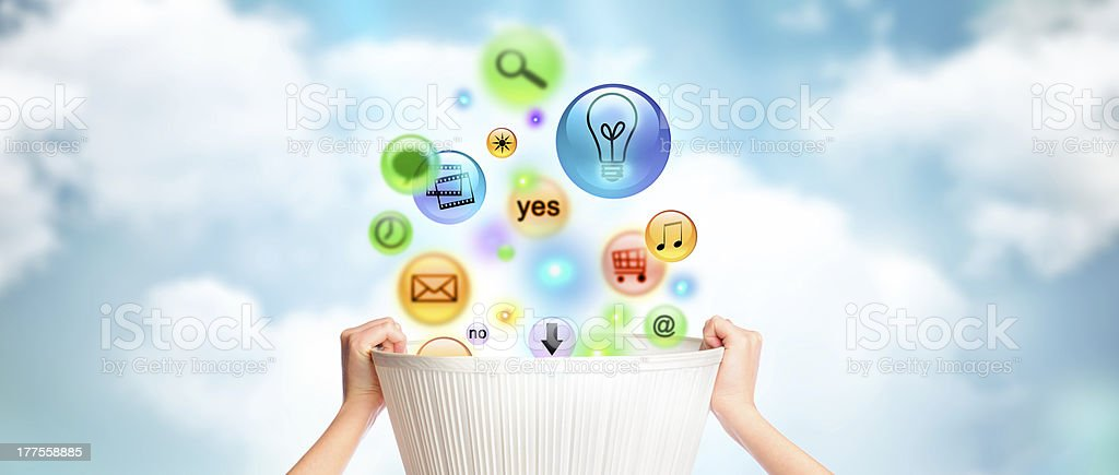 Humans hands holding a basket with lots of different icons stock photo