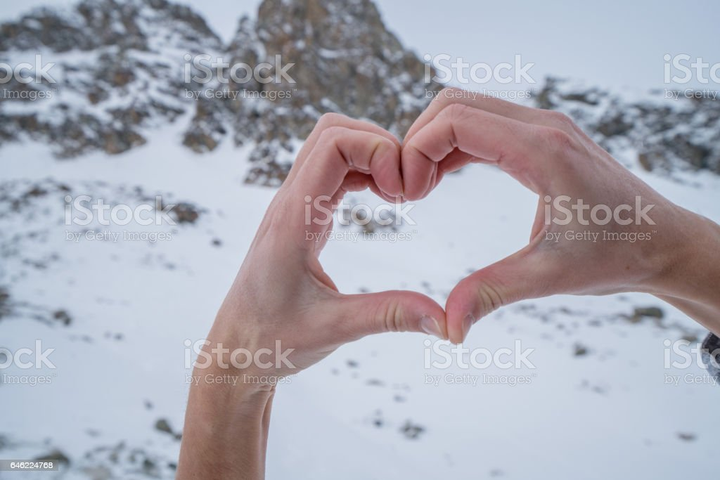 Human's hands making heart shape on snowy mountains landscape stock photo