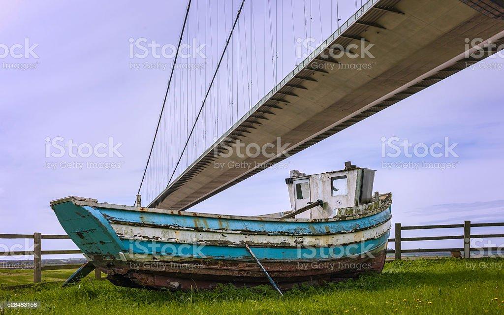 Humber Bridge and derelict fishing boat. stock photo