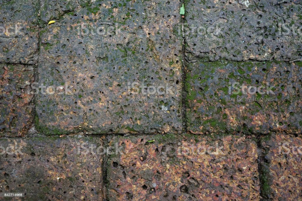 Humid rusty red brick stone laterite pavement block pattern background with green lichen stock photo