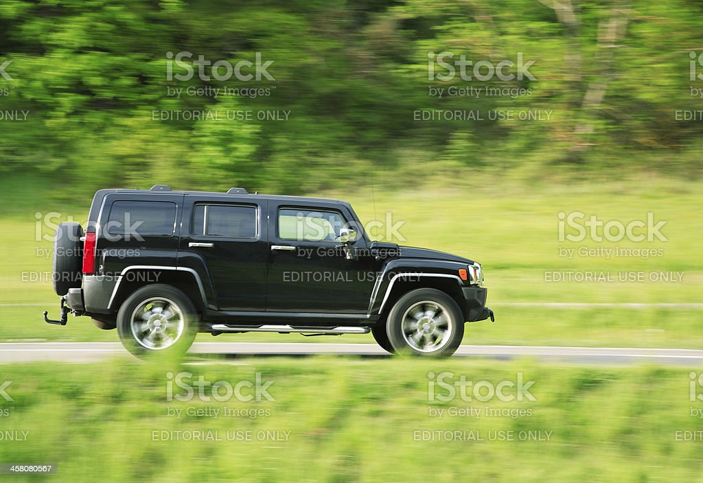 Hummer H3 Driving on Country Road in Spring stock photo