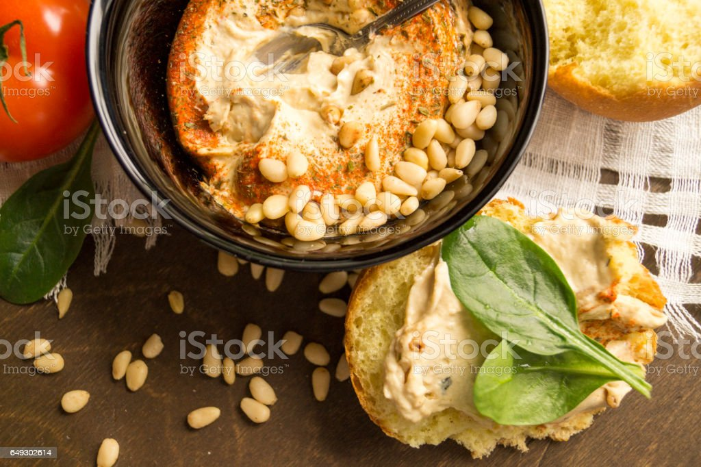 hummus appetizer with pine nuts on wooden table stock photo