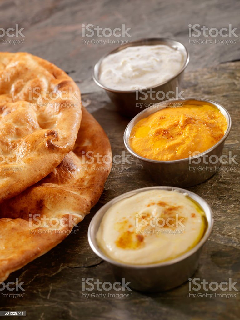 Hummus, Red Pepper Hummus and Tzatziki Sauce With Flat Breads stock photo