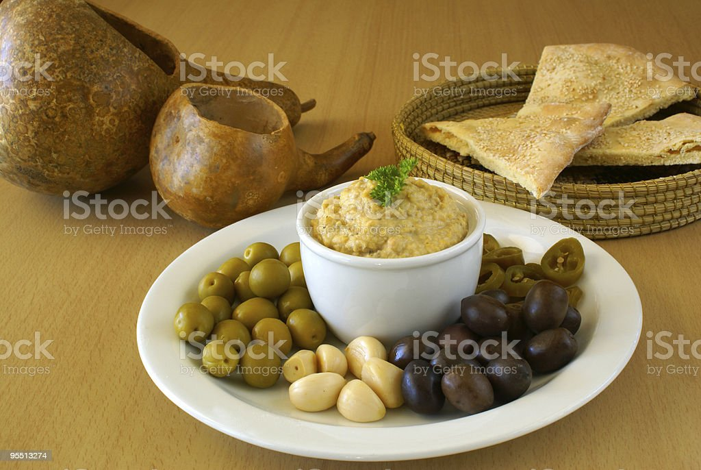Hummus with assorted olives and pickles royalty-free stock photo