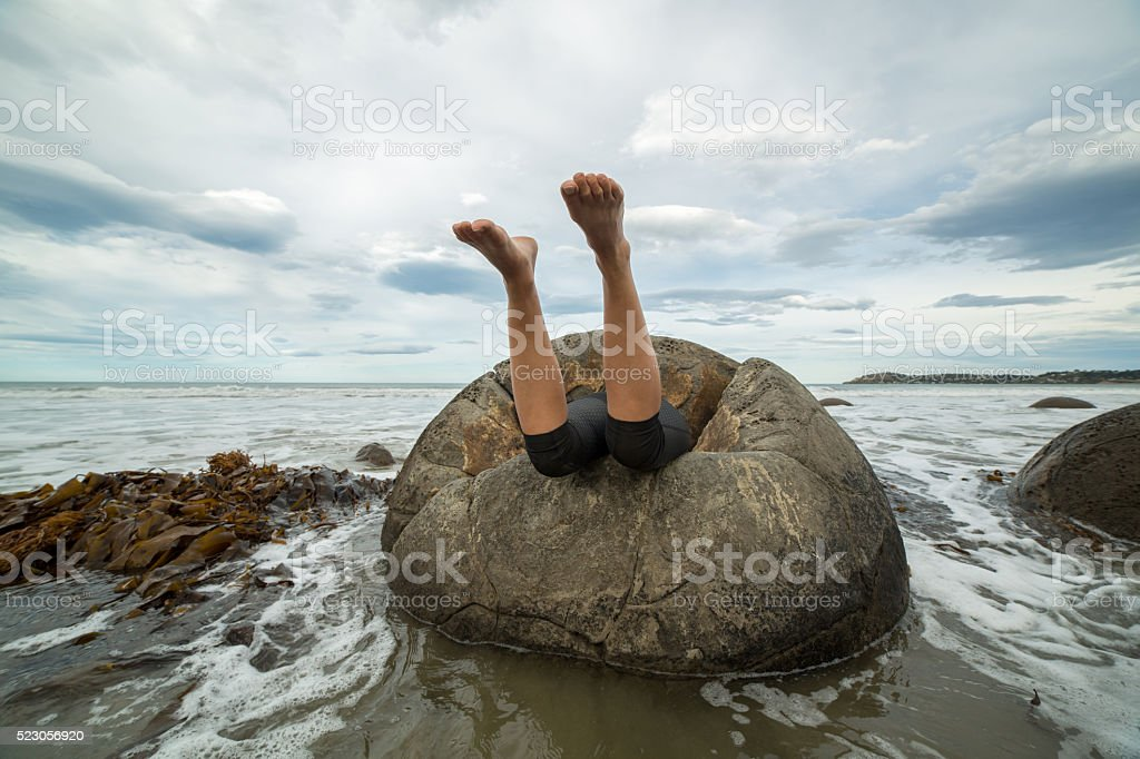 Humor picture: Woman eaten by spheric boulder on beach stock photo