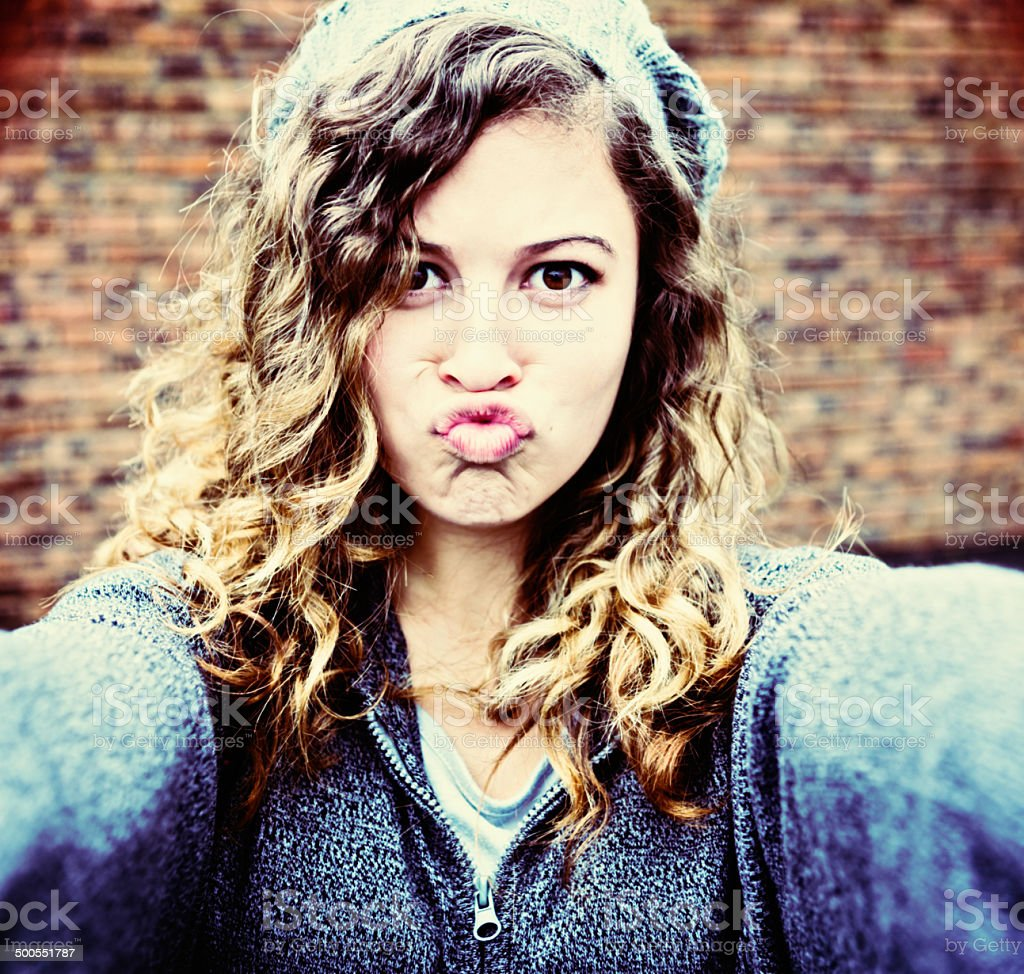 Humorous, exaggerated trout-pout from cute young woman taking Selfie stock photo