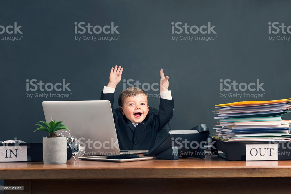 Humorous image of young boy working on a laptop computer stock photo