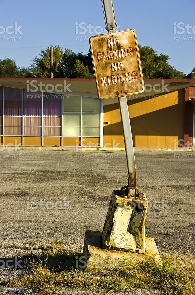 Humorous No Parking Sign Heavily Damaged by Cars stock photo