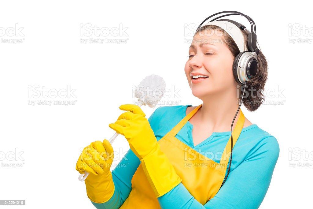 humorous photo housewife with headphones and  brush  toilet stock photo