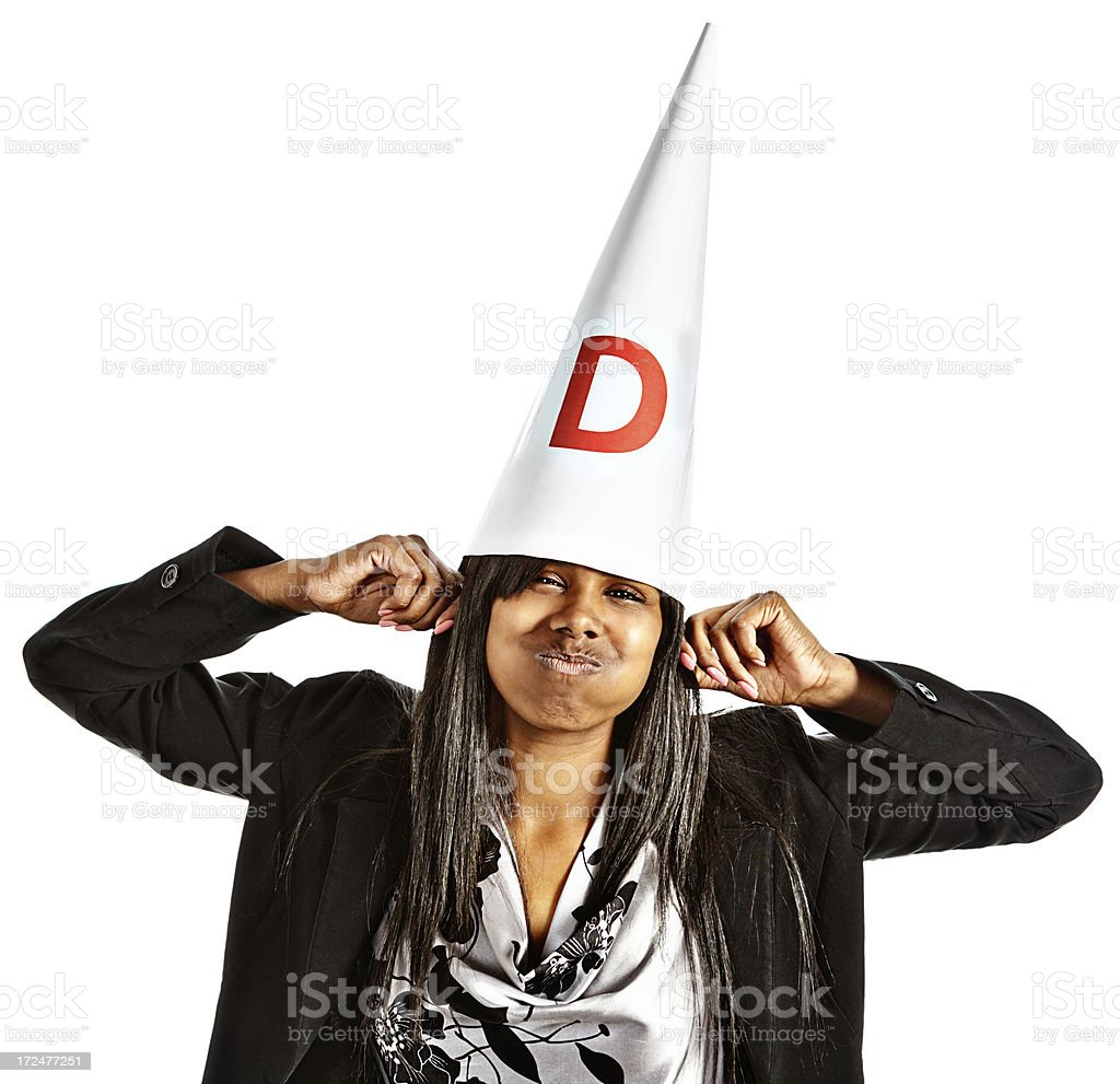 Humorous portrait of zany woman in dunce cap grimacing playfully royalty-free stock photo