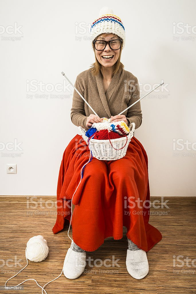 Humorous, woman is sitting in chair and knitting winter caps royalty-free stock photo