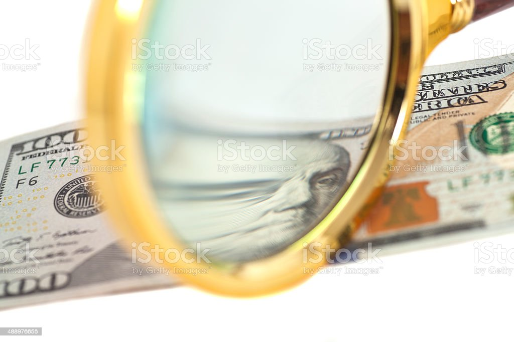 Hundred dollar banknote under magnifying glass isolated stock photo
