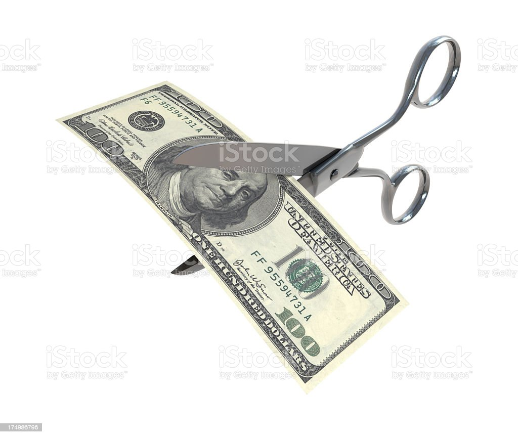Hundred dollar bill being cut in half with scissors stock photo