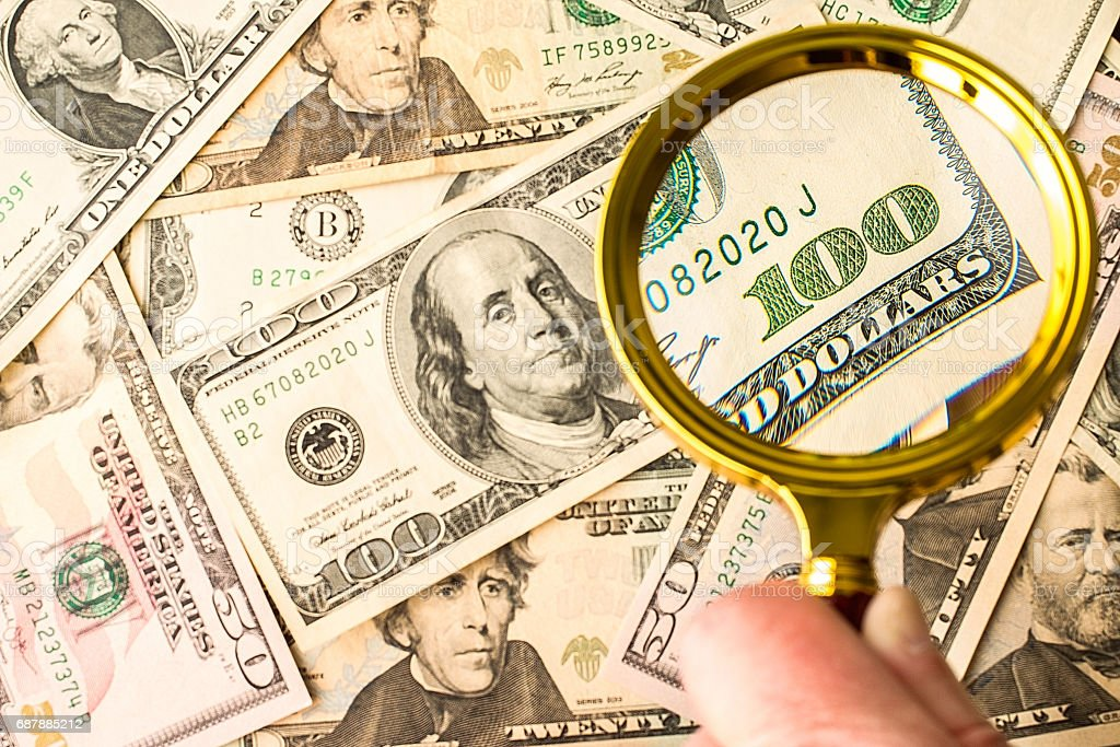 Hundred dollar bill under a magnifying glass stock photo