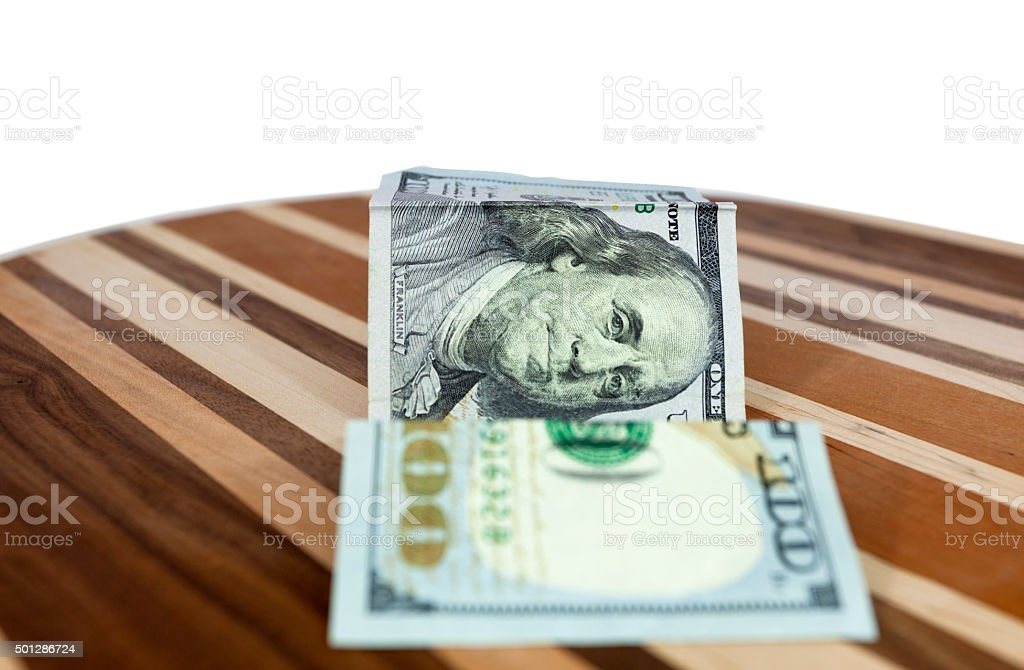 Hundred Dollar Bill with Folds on Parque Table stock photo