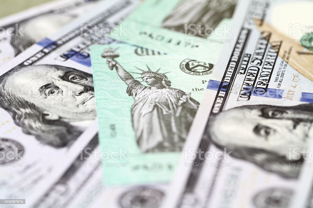 Hundred dollar bills with US Treasury checks stock photo