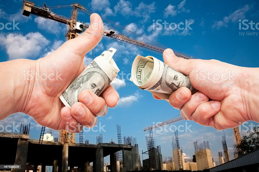 Hundred dollar notes  in a hand against a construction stock photo
