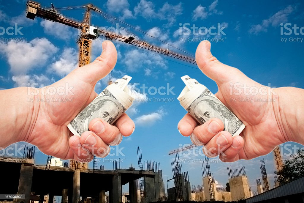 Hundred dollar notes  in a hands against a constructio stock photo