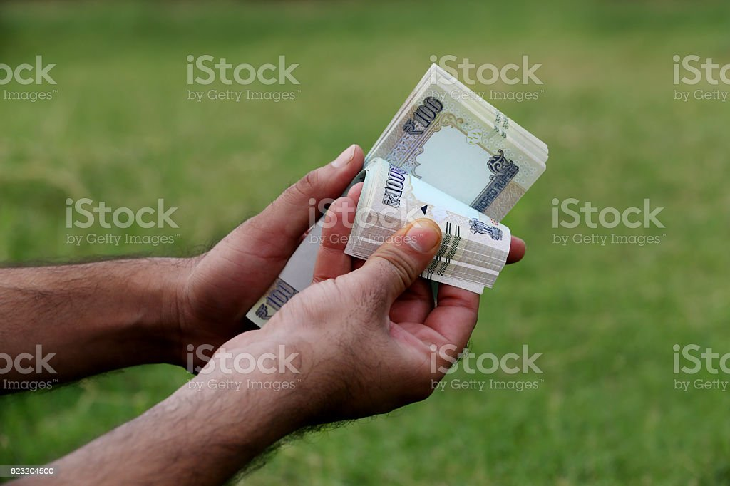 Hundred notes in hand (Indian Currency) stock photo