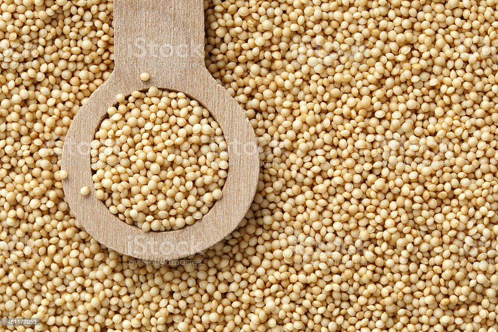 Hundreds of Amaranth Seeds in Wood Measuring Spoon stock photo